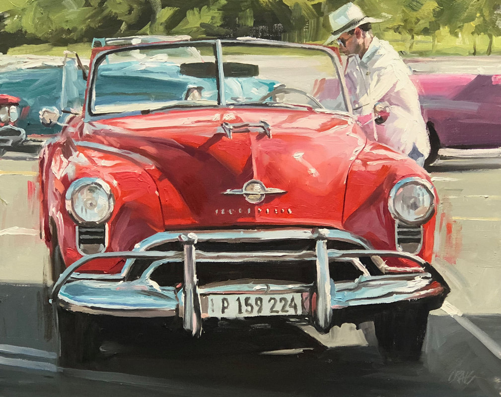 Dapper man on driver side of 1950's red convertible