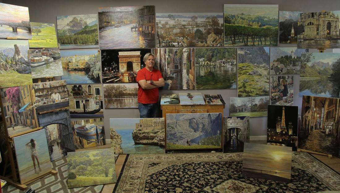 Photograph of Craig Nelson in studio surrounded by oil paintings
