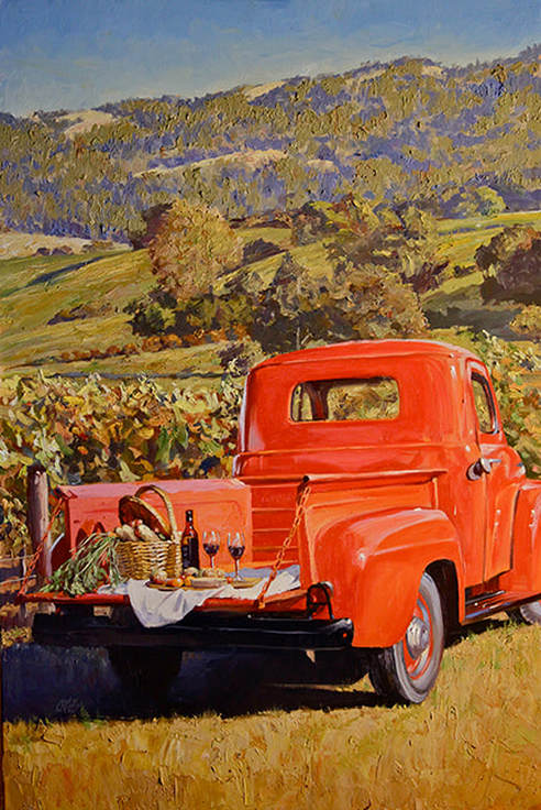 Classic red truck with picnic on tail bed in front of vineyard landscape