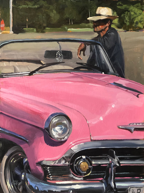 Man in brimmed hat leaning on pink 1950s Chevrolet convertible