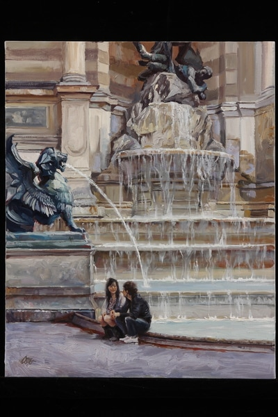 Young couple seated before a fountain